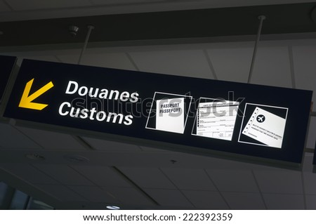 Bilingual customs and passport control sign at international airport.