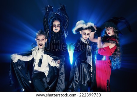 Cheerful children in halloween costumes posing over dark background. #222399730