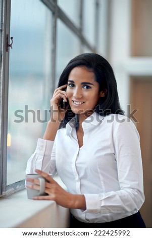 Happy businesswoman on work call with coffee and window smiling #222425992