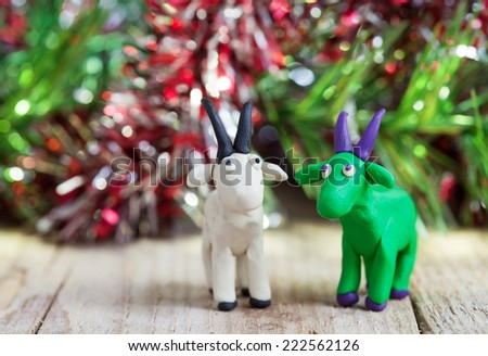 Plasticine world - little homemade white and green goat with purple horns and hooves stand on a wooden floor, selective focus and place for text