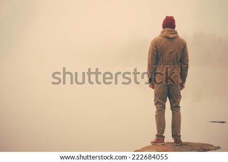 Young Man standing alone outdoor with foggy scandinavian nature on background Travel Lifestyle and melancholy emotions concept film effects colors #222684055
