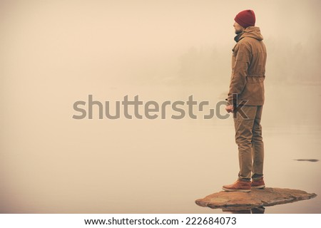 Young Man standing alone outdoor with foggy scandinavian nature on background Travel Lifestyle and melancholy emotions concept film effects colors #222684073
