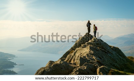 Two female hikers on top of the mountain enjoying valley view, Ben A'an, Loch Katrine, Highlands, Scotland, UK #222799717