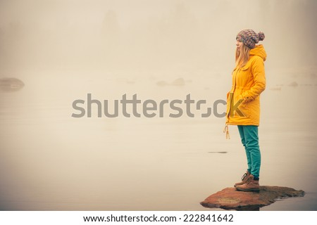 Young Woman standing alone outdoor Travel Lifestyle and melancholy emotions concept  winter foggy nature on background  #222841642