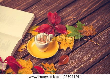 Autumn leafs, book and coffee cup on wooden table. #223041241
