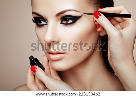 Makeup artist applies eye shadow. Beautiful woman face. Perfect makeup #223153462