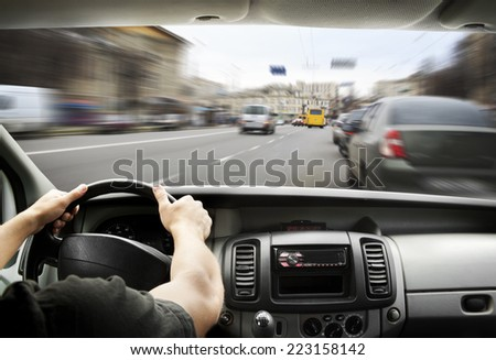Man's hands of a driver on steering wheel of a minivan car on asphalt road #223158142
