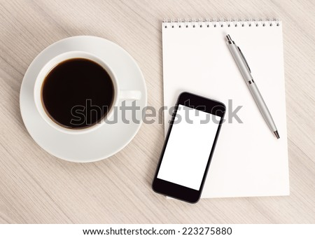 Computer desk with a cup of coffee, a notebook and pen #223275880