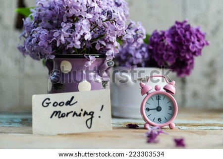 Two tone Lilac flowers in a ceramic pots white and purple, with pink vintage tiny alarm clock and a Good Morning note on a shabby wooden surface