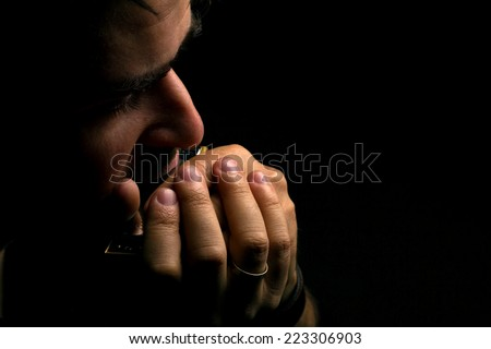 brunette man playing on harmonica on dark background with place for your text #223306903
