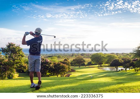 Man hitting golf ball down hill towards ocean and horizon Royalty-Free Stock Photo #223336375