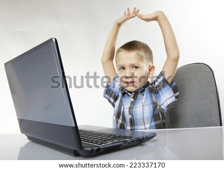 Triumphing child boy with a laptop notebook computer on white background. Computer addiction. #223337170
