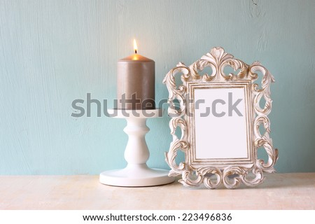 image of vintage antique classical frame and burning candle on wooden table