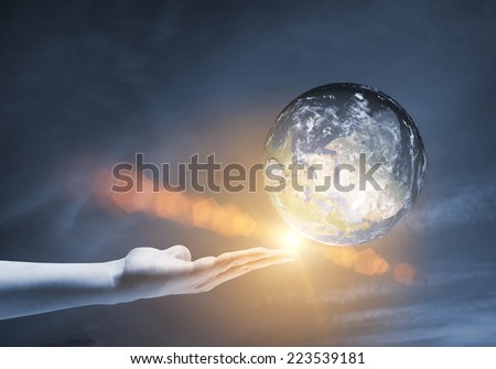 Human hand holding Earth planet. Elements of this image are furnished by NASA #223539181