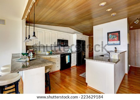 Kitchen room with paneled ceiling, white cabinets with black appliances. Granite counter top with bar stools #223629184