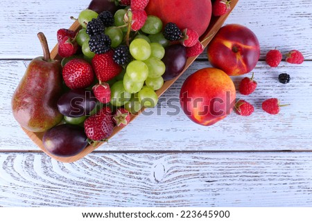 Different berries and fruits on wooden table close-up #223645900