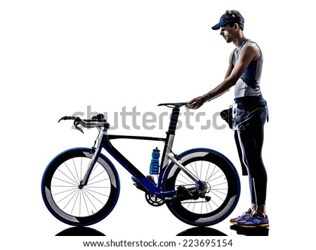 man triathlon iron man athlete standing with all his equipment in silhouette on white background