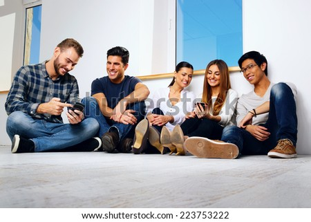 Portrait of a smiling friends sitting on the floor and looking at smartphone #223753222