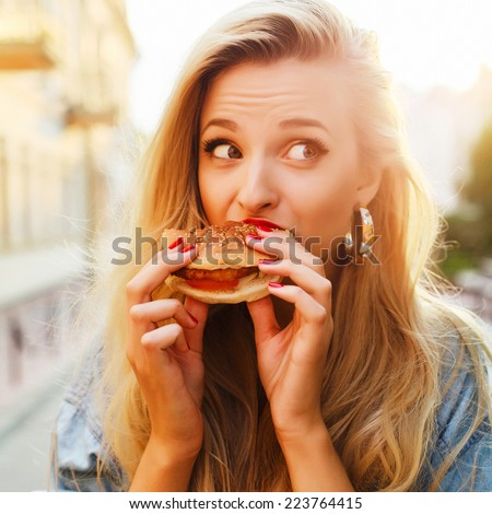 Pretty young blonde funny woman eating hamburger outdoor on the street  #223764415