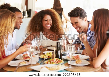 Group Of Young Friends Enjoying Meal In Outdoor Restaurant Royalty-Free Stock Photo #223908613