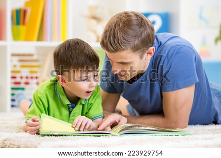 kid boy and his father read a book on floor at home #223929754