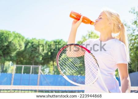 thirsty athlete. tennis player drinking power drink