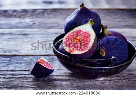figs on a dark wood background. tinting. selective focus on the front figs slice in the bowl #224018086