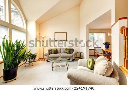 Luxury family room in soft creamy tones with high ceiling and arch window. Room with love seat and armchair, glass top coffee table, decorated with green plants