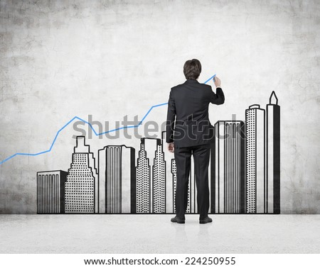 Young professional drawing a growing real estate chart. Concrete background.  #224250955