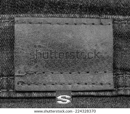 gray leather label on gray denim  background, size  #224328370
