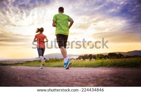Cross-country trail running people at sunset. Runner couple exercising outside as part of healthy lifestyle. #224434846