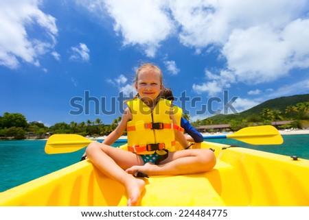 Little girl enjoying paddling in colorful yellow kayak at tropical ocean water during summer vacation #224484775