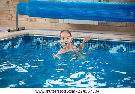 Portrait of young girl learning how to swim in pool #224557534