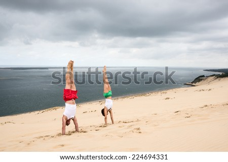 PYLA SUR MER, FRANCE - JULY 5, 2014: A woman and a man stand upside down on the dune of pilat, which is the highest sand dune in Europe.  #224694331