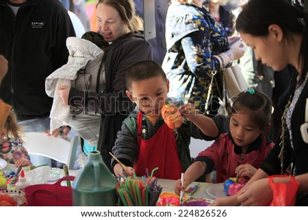 NEW YORK CITY - OCTOBER 19 2014: the Lower East Side's Orchard Street Pickle Day fair brought dozens of food & snack vendors into contact with hundreds of passersby. Kids paint pumpkins #224826526