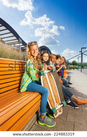 Nice girls sitting on wooden bench in urban style #224883319