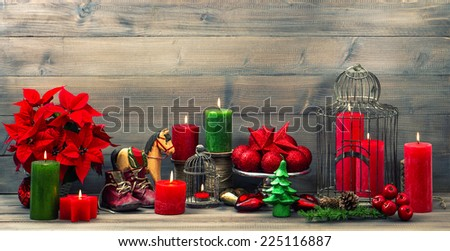 christmas decorations with red candles, flower poinsettia, stars and baubles. vintage style toned picture