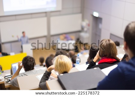 Professor giving presentation in lecture hall at university. Participants listening to lecture and making notes. Royalty-Free Stock Photo #225178372