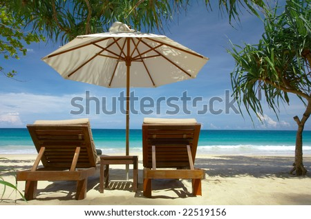 view of two chairs and white umbrella on the beach. #22519156