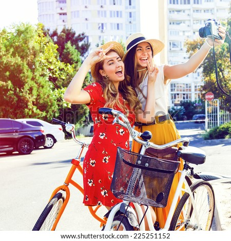 Two pretty young happy girls making selfie on retro camera, laughing going crazy and have great time, walking with vintage bikes in the city. Instagram bright colors.