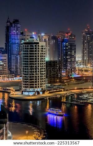DUBAI, UAE - SEPTEMBER 29, 2012: Night view at modern skyscrapers in Dubai Marina. United Arab Emirates. Dubai Marina - artificial canal city, carved along a 3 km stretch of Persian Gulf shoreline.  #225313567