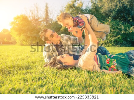 happy and playful parents with kid. Mom holding up his son at the park #225335821