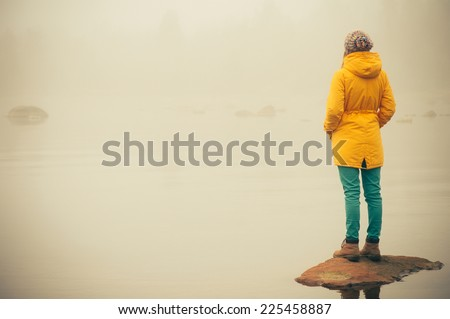 Young Woman standing alone outdoor Travel Lifestyle and melancholy emotions concept  winter foggy nature on background  #225458887