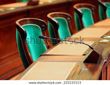 Empty vintage congress hall with seats and microphones. Royalty-Free Stock Photo #225535513