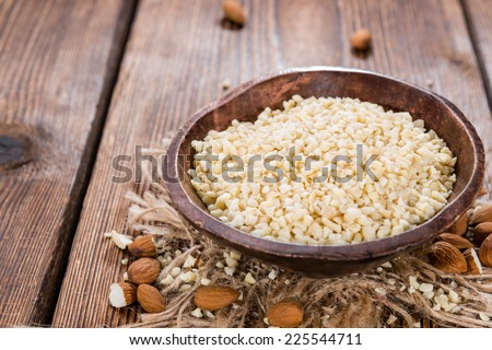 Small bowl with Minced Almonds (close-up shot) on rustic wooden background #225544711