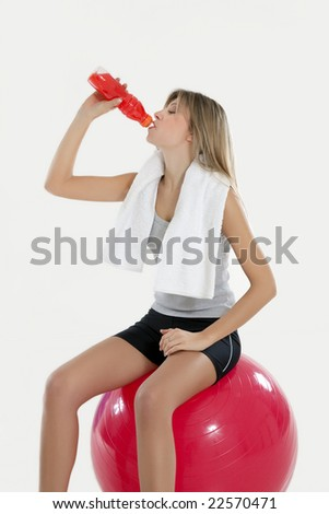 young woman sitting on fitness ball in gym and drinking gatorade