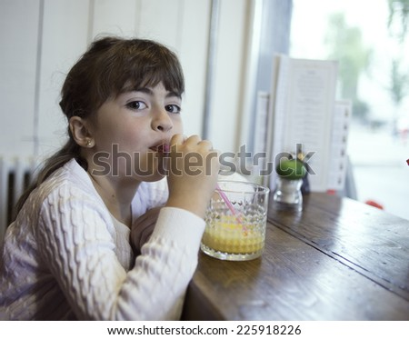 Little girl having an orange juice at the table #225918226
