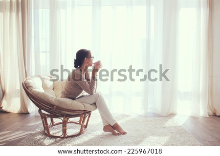 Young woman at home sitting on modern chair in front of window relaxing in her living room and drinking coffee or tea #225967018