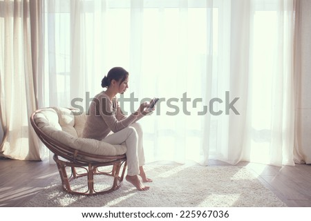 Young woman at home sitting on modern chair in front of window relaxing in her living room using tablet pc #225967036