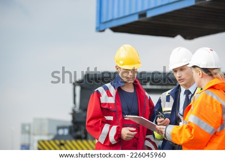 Workers discussing over clipboard in shipping yard #226045960